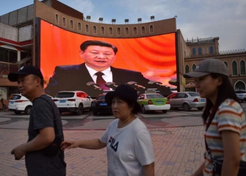 中國大量的網格員在各自轄區中,緊密監控人民的日常生活。圖中,中國國家主席習近平發表講話的影像,在中國新疆街頭播送。(資料照,法新社)