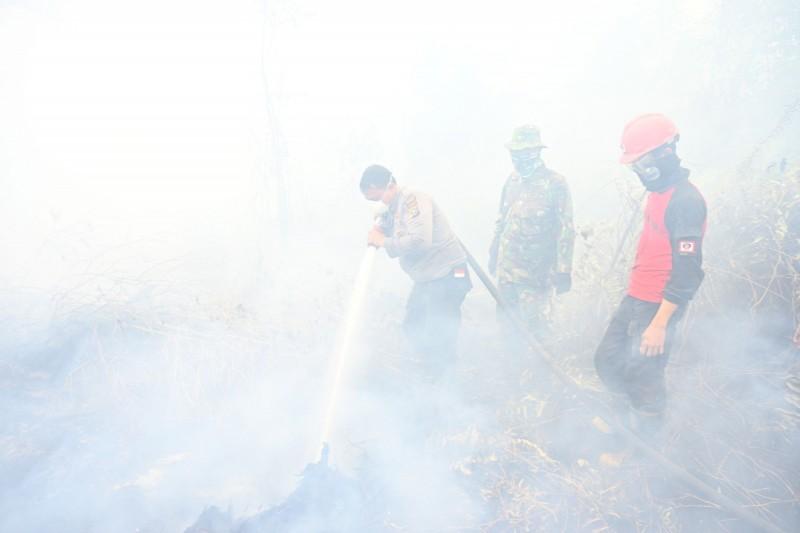 印尼成千上萬名消防員正如同「打地鼠」般奮力滅火,以對抗看不見的敵人─加劇全球暖化的泥炭地下火。(法新社)