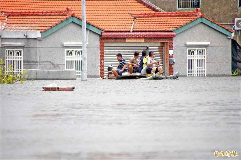 去年嘉義縣東石鄉掌潭村嚴重淹水,居民靠船筏進出。(資料照,記者林宜樟攝)