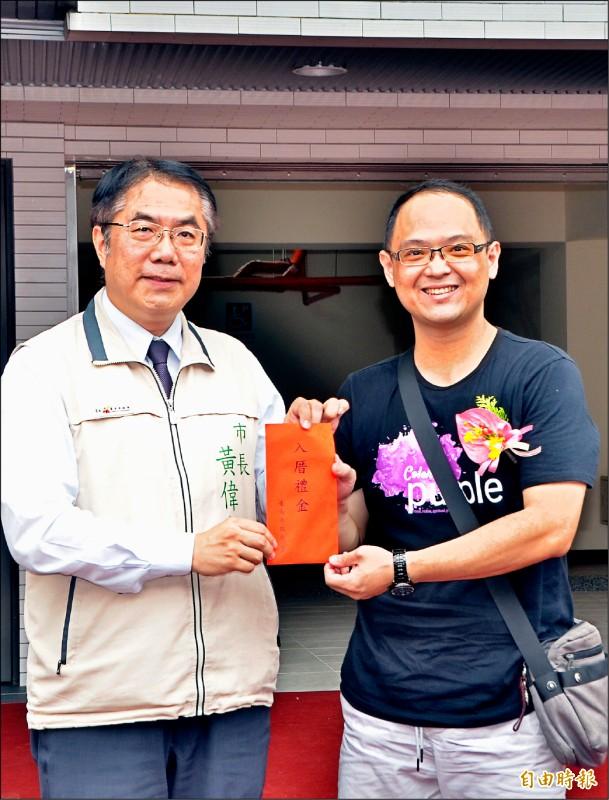 台南市長黃偉哲(左)向居民祝賀,並頒給居民入厝禮金。 (記者吳俊鋒攝)