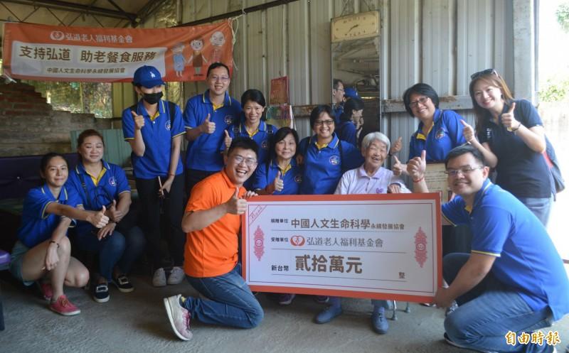 中國人文生命科學永續發展協會志工今天探視太平山區獨居長輩,並捐贈20萬元給弘道基金會,支持幫長輩送餐的服務。(記者陳建志攝)