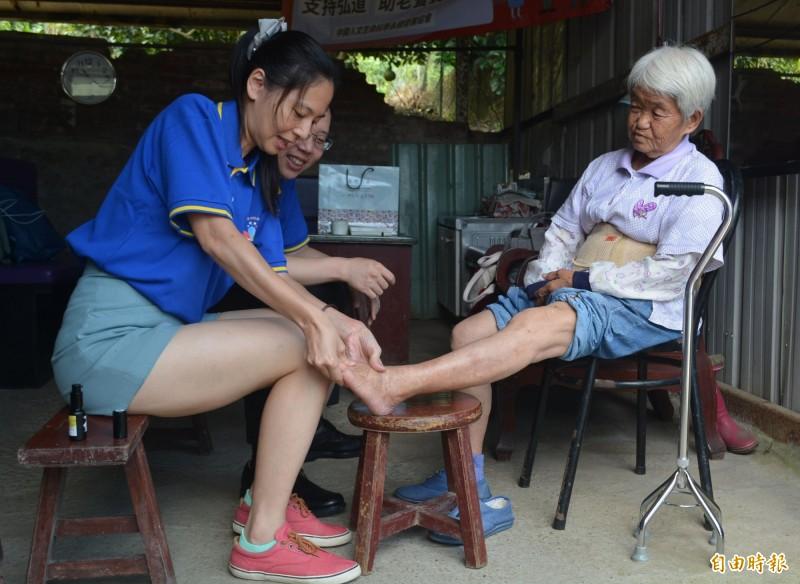 中國人文生命科學永續發展協會今天出動10多位志工到太平山區探視獨居的賴廖玉枝阿嬤(右),還幫她按摩腳。(記者陳建志攝)