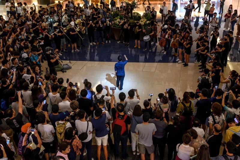 有香港網友今日發起晚上在九龍塘舉行快閃音樂會,以樂器表演反修例歌曲《願榮光歸香港》。(法新社)
