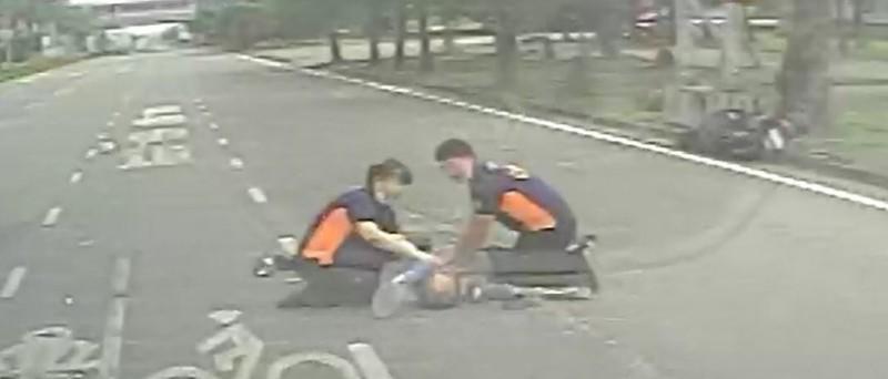 載送病患的救護車在路口撞上機車騎士,救護人員趕緊下車為失去意識的機車騎士進行CPR。(記者李立法翻攝)