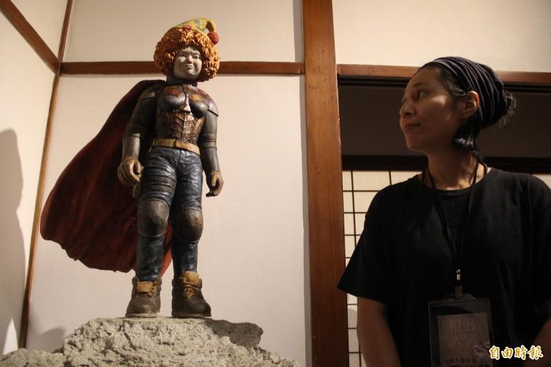 石佳蕙作品「極度英雄」作品頭部是小丑,身體是英雄裝扮,象徵人的困惑及掙扎,運用了樟木、銅、油彩顏料等異材質的結合。(記者許倬勛攝)