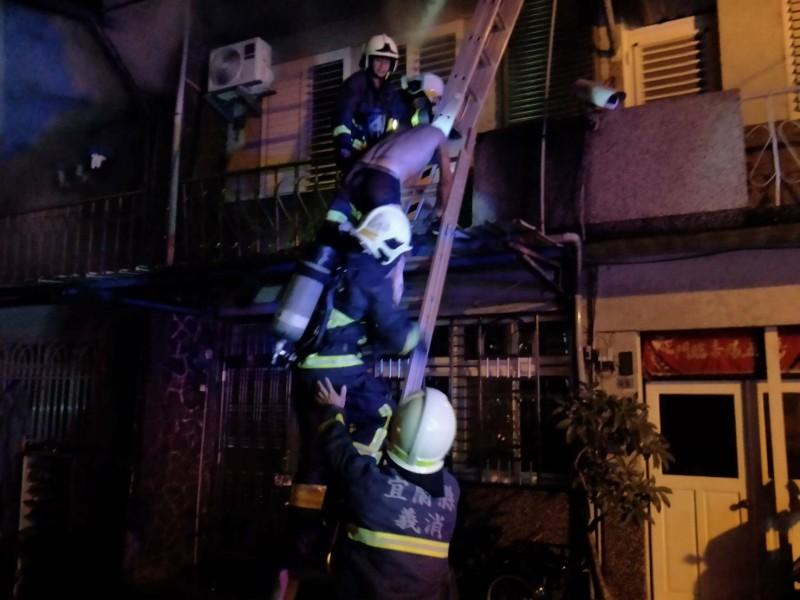 消防人員架梯上樓救人。(記者江志雄翻攝)