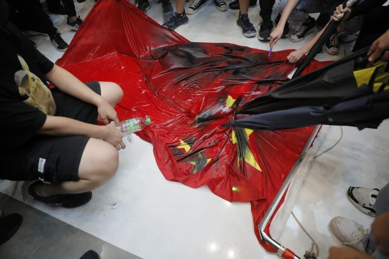 香港抗議群眾潑濕、噴汙中國五星旗。(美聯社)