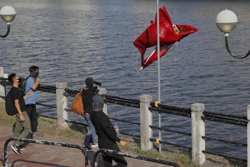 示威者把汙損的五星旗拋入城門河中。(美聯社)