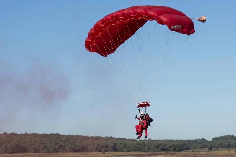 第二次世界大戰市場花園行動75週年紀念日,97歲的英國老兵科爾特曼(Sandy Cortmann)在降落傘團的幫助下雙人跳傘著路。(美聯社)
