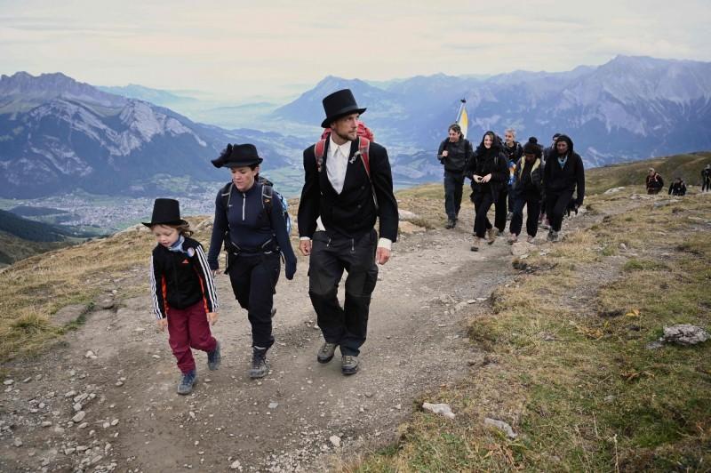 「送葬隊伍」成員穿黑衣爬上位於瑞士東北部的皮措爾山。(法新社)