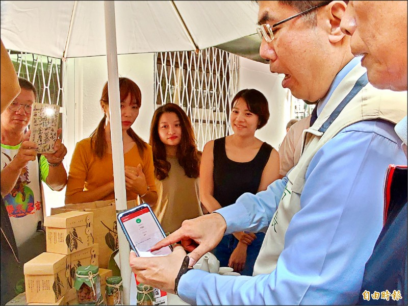 台南市長黃偉哲在府中街以手機消費體驗行動支付。(記者蔡文居攝)