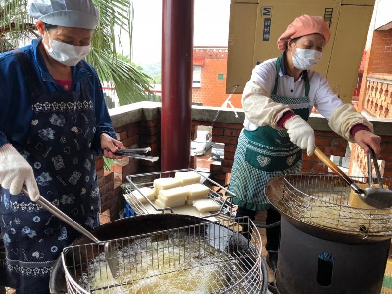 志工們忙著準備美食給仁愛之家的長輩享用。(社會局提供)