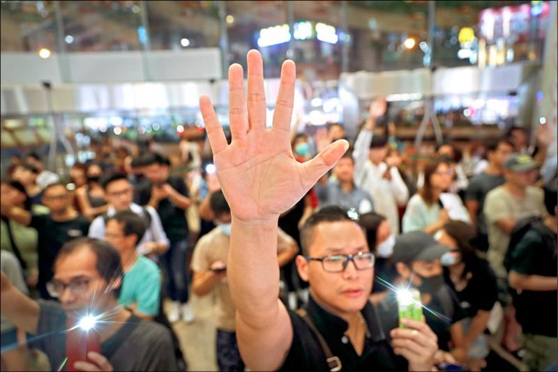 二十五日又有大批香港民眾在商場聚集,高舉五指強調「五大訴求,缺一不可」,並合唱「願榮光歸香港」。(美聯社)
