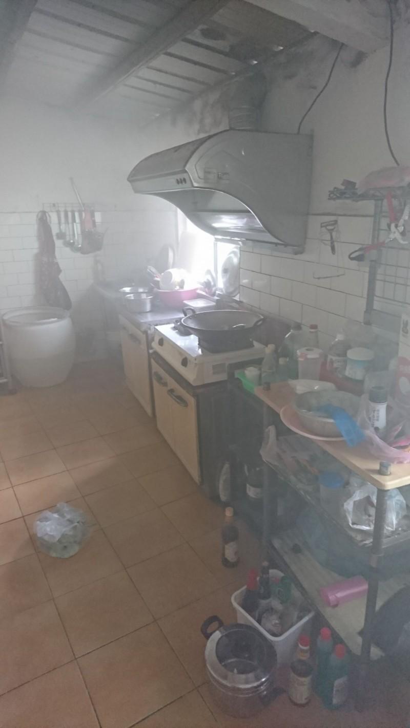 民宅廚房「起火」,員警勇闖火場滅火,還得應付惡犬的追趕。(記者蔡政珉翻攝)