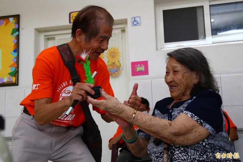 74歲的不老騎士林嘉中(左)教長照中心的阿嬤變魔術。(記者廖淑玲攝)