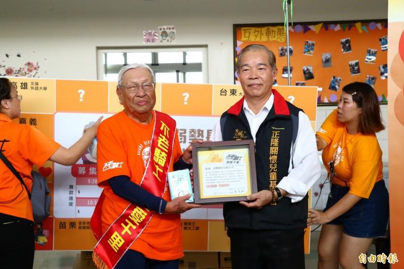 此行最高齡94歲的郭深森(左)代表不老騎士致贈感謝狀給贊助單位。(記者廖淑玲攝)