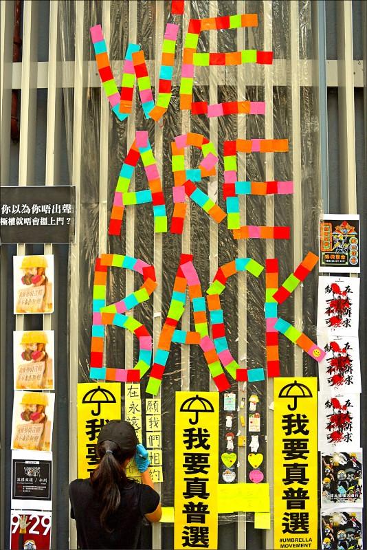 紀念「雨傘運動」五週年,香港政府總部外牆廿八日重現「元祖連儂牆」面貌,張貼反送中海報等文宣。(法新社)