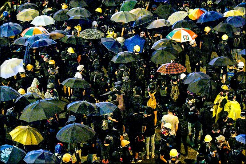 「雨傘運動」五週年,香港政府總部外又發生警民衝突,示威者以傘陣對抗水砲車。(法新社)