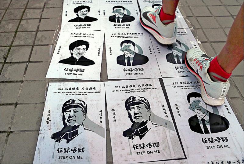 香港灣仔一處「連儂之路」貼有習近平、毛澤東、林鄭月娥圖像,任人踐踏。(路透)