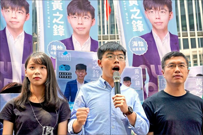 香港社會運動代表人物黃之鋒(中),廿八日在他五年前展開重奪政府總部東翼「公民廣場」行動的現場,宣布人生初次參選決定,將投入十一月廿四日香港區議會選戰。(美聯社)