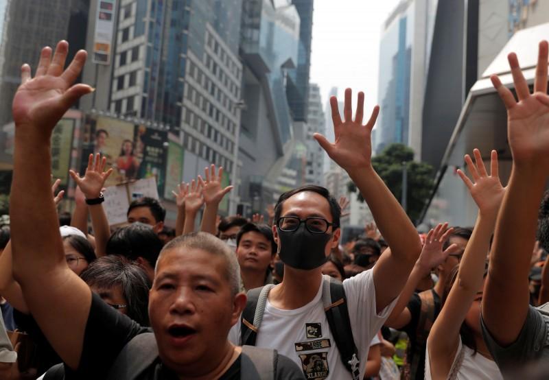 香港示威者高舉單手,並不斷高喊「Five demands Not one less」。(路透)