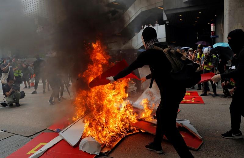 有示威者拆除慶祝中國國慶的標語,進行焚燒。(路透)