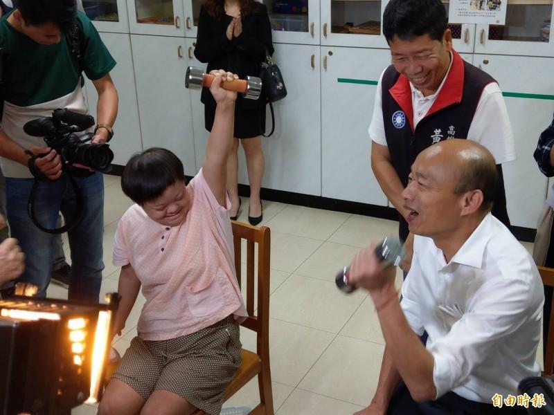 韓國瑜(右)今晚夜宿無障礙之家,並與重度智能障礙者小穎比賽舉啞鈴。(記者方志賢攝)