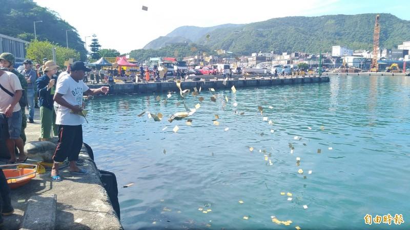 漁工同鄉在岸邊灑冥紙。(記者江志雄攝)