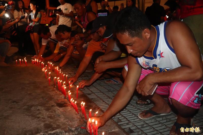 漁工們點起百支蠟燭追思罹難友人。(記者林敬倫攝)
