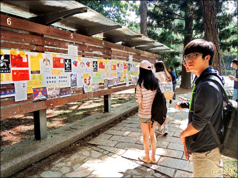 清大學生會在校內野台設置的連儂牆,九月卅日中午遭一名撐傘女子撕毀三張海報,學生會除報警,更譴責這種行為。(記者洪美秀攝)