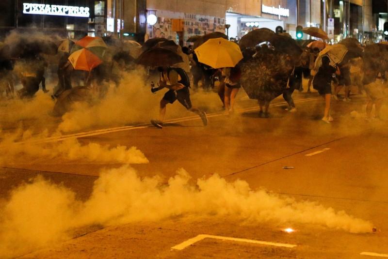 香港多區今晚持續有「反送中」集會示威,警察在港島太古地鐵站附近發射催淚彈驅散人群。(路透)