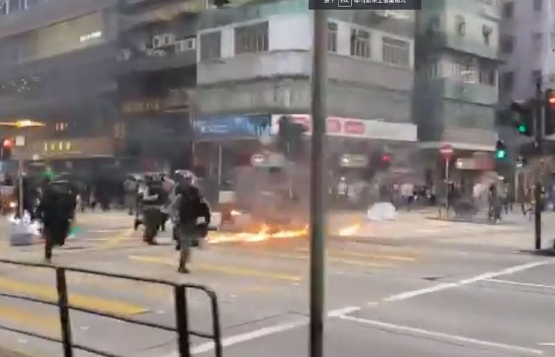 香港記者紀錄下警方在街頭閃過火堆,整隊人馬追趕示威者的景象。(擷取自「Hong Kong Free Press」推特影片)