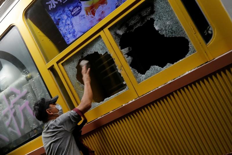 示威者拿硬物打破美心快餐廳的玻璃。(路透)