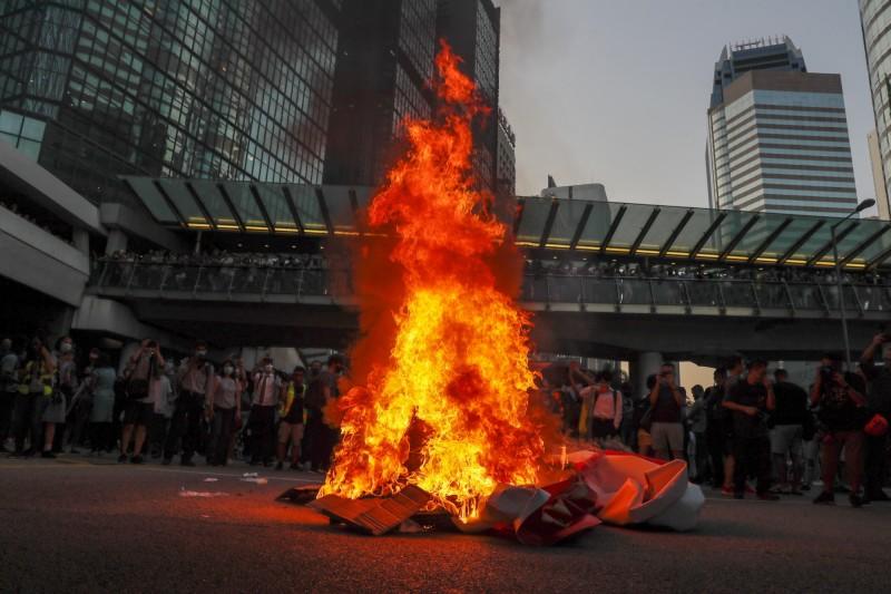 示威者聚集在香港中環抗議《禁蒙面法》,並焚燒中國70週年國慶布條。(法新社)