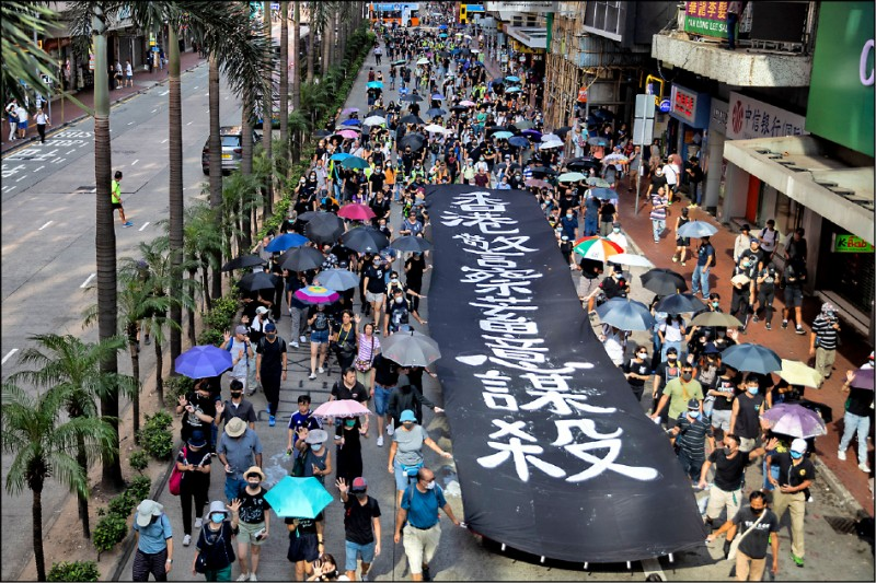 示威者五日在灣仔高舉「香港警察蓄意謀殺」標語。(彭博)