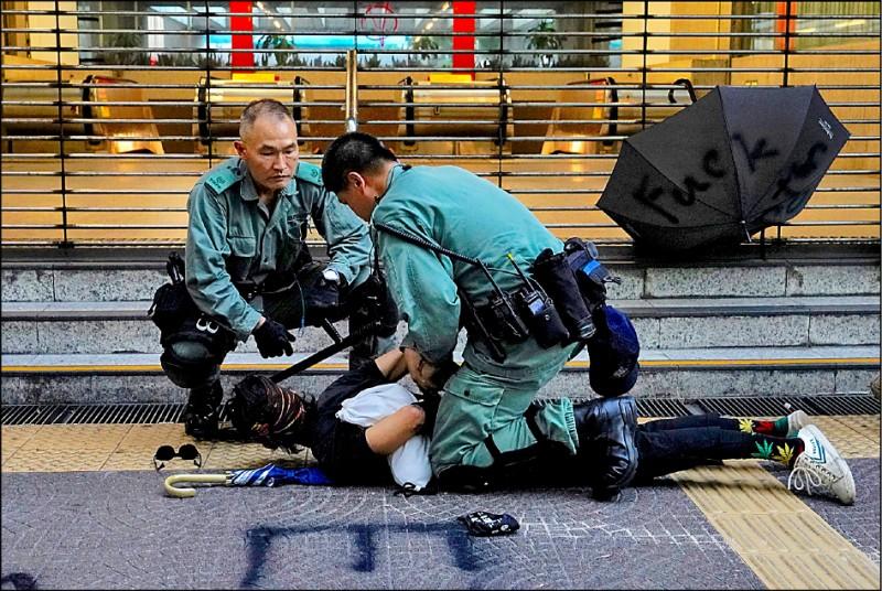 一名示威者五日在港鐵站外遭警方壓制。(美聯社)