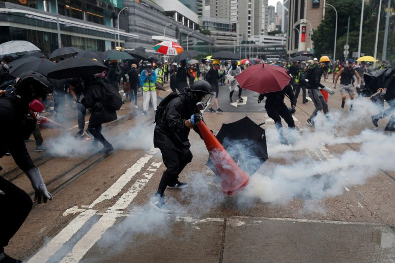 示威者嘗試以交通錐及水澆熄催淚彈。(路透)