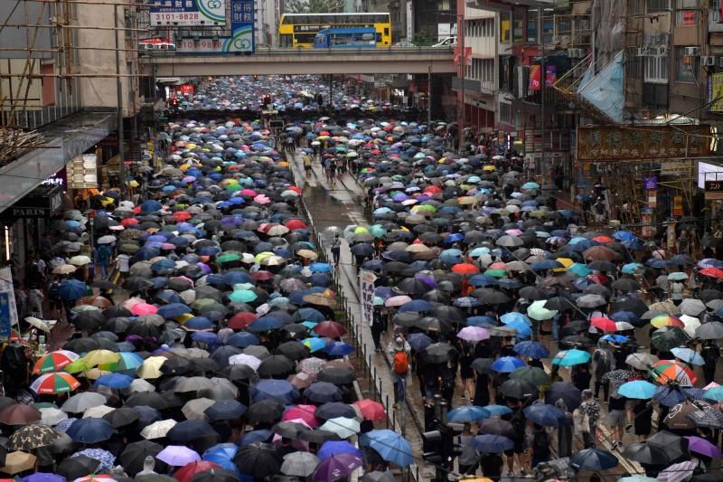 群眾撐起雨傘在風雨中同行,並佔據軒尼詩道所有車道。(法新社)