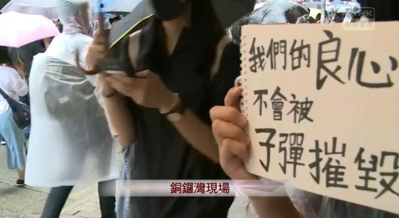 有民眾手持「我們的良心不會被子彈摧毀」標語。(擷取自《香港電台》直播畫面)