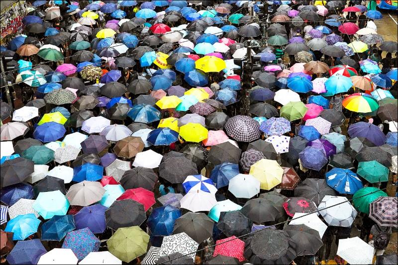 不滿香港政府頒佈實施《禁止蒙面規例》,數萬民眾6日下午自發性在港島、九龍等地,兵分多路冒雨上街抗爭。(美聯社)