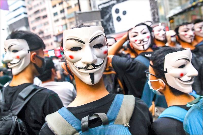遊行期間,示威者多以口罩蒙面,毫不理會蒙面禁令,隊伍中還穿插「全副標準武裝」 的「勇武派」示威者。(歐新社)