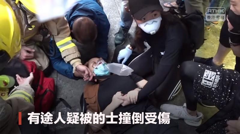 昨日香港示威期間1輛計程車衝撞人行道,造成3人受傷,其中1名女子左小腿骨折。(擷取自「香港電台視像新聞 RTHK VNEWS」Facebook粉絲專頁)