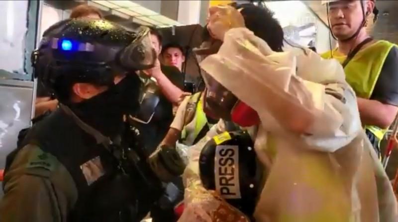 日前通過《禁蒙面法》引起極大爭議,昨晚警方的清場行動中,有警員強逼現場記者脫下防毒面具。(圖擷取自《南華早報》推特影片)