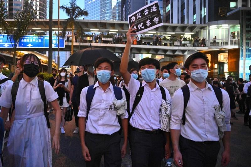 明(8日)為禁蒙面法實施後的首個上學日,傳出香港教育局要求全港中學明早上報校內戴口罩學生人數。(法新社)