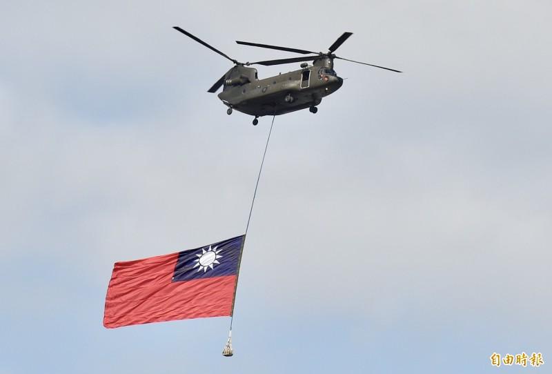國慶大會今天下午最後彩排,陸軍航特部運輸直升機吊掛巨型國旗飛越觀禮台。(記者塗建榮攝)