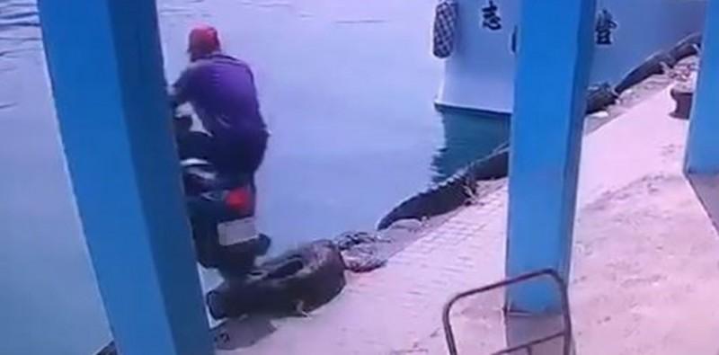 1名紫衣阿伯7日中午在小琉球大福漁港騎車,不料與手推車碰撞,在失去重心之下衝入海。(圖擷取自爆廢公社)