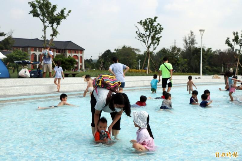 天氣炎熱,不少孩童在水池內消暑。(記者萬于甄攝)