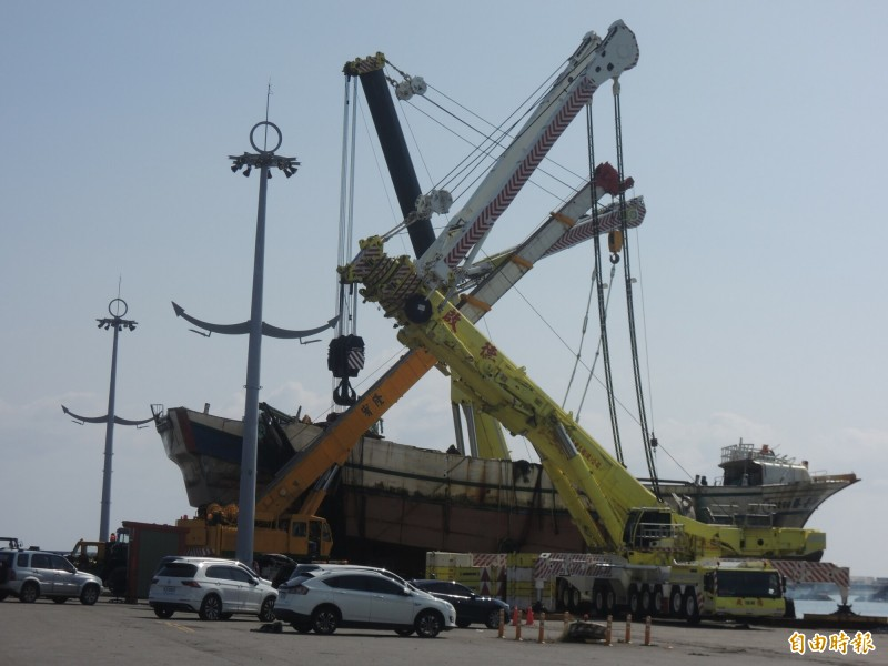 台北港務公司出動全國最大的1200噸級吊車(右),把新臺勝266號漁船吊上岸。(記者江志雄攝)