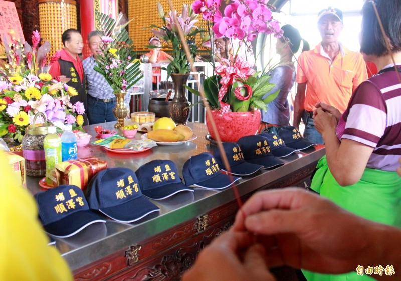 國慶連假,埔鹽順澤宮每日發送1000頂免登記冠軍帽,民眾將帽子放在供桌,祈求平安順利。(記者陳冠備攝)