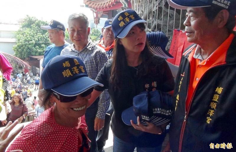 埔鹽鄉長許文萍(右2)將原本頭上戴的順澤宮帽子給不方便排隊的女長輩,讓長者開心的笑了。(記者陳冠備攝)